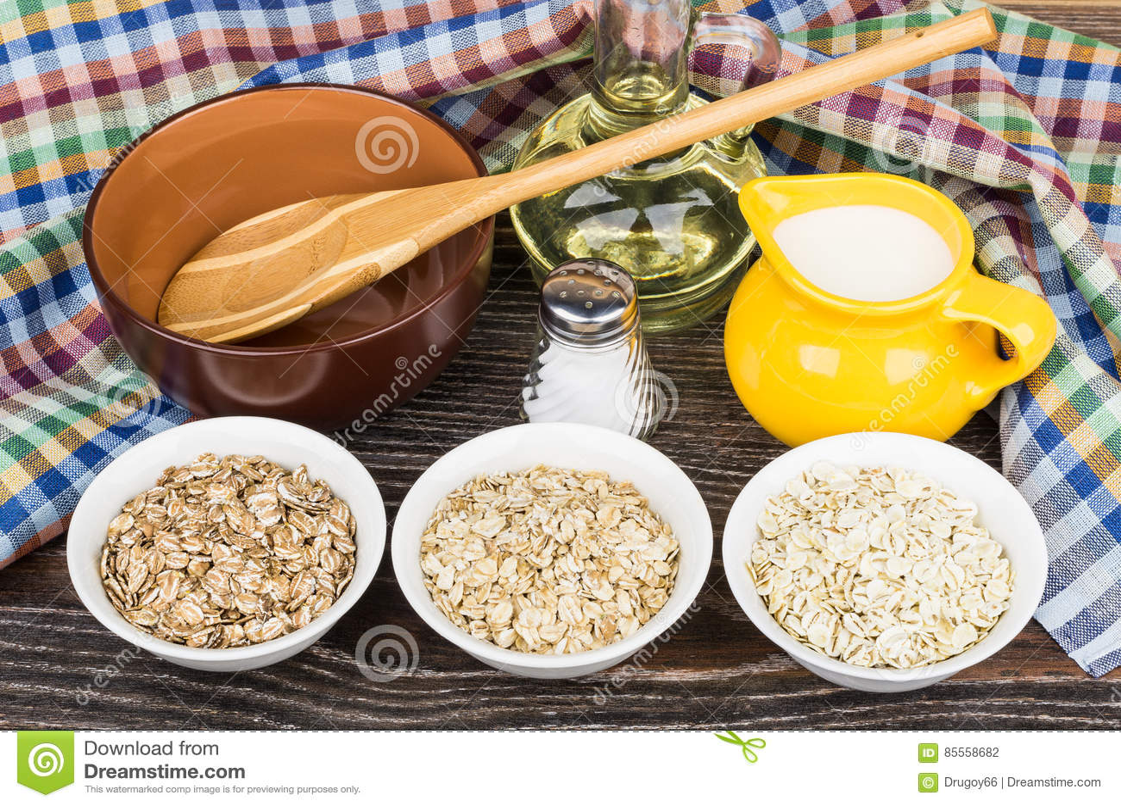Schüsseln mit Hafer, Roggen, Gerste blättert, Krugmilch, Salz ab