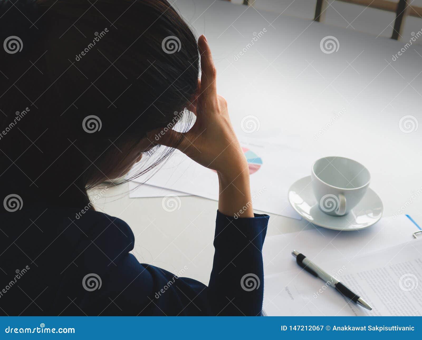 Sch?ne Gesch?ftsfrau des asiatischen langen Haares in der Marineblau-Klagenbelastung mit Arbeit util-Kopfschmerzen in ihrem B?ro