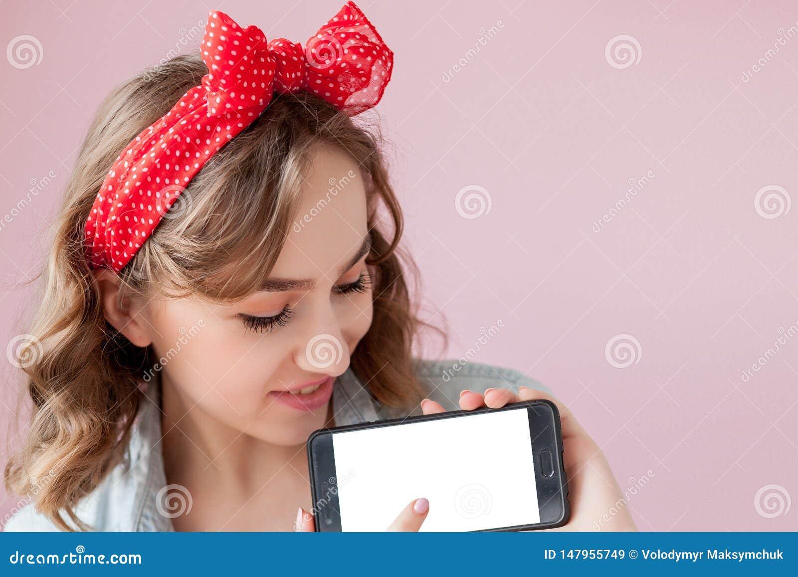 Sch?ne junge Frau mit Stift-obenmake-up und -frisur ?ber rosa Hintergrund mit Handy mit Kopienraum