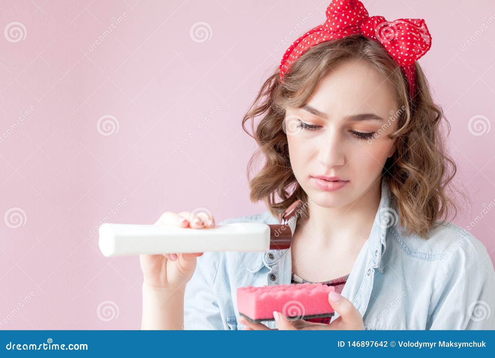 Sch?ne junge Frau mit Stift-obenmake-up und -frisur mit Reinigungswerkzeugen auf rosa Hintergrund