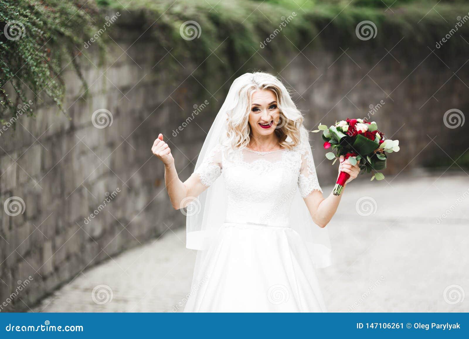 Sch?ne junge Luxusbraut im Hochzeitskleid, das im Park aufwirft