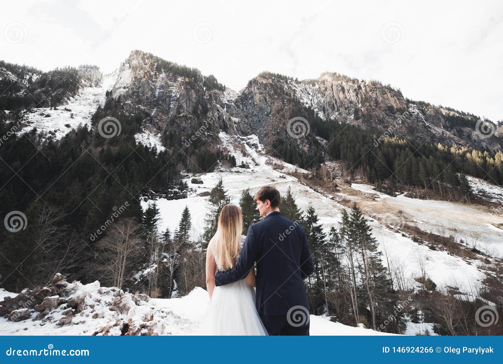 Sch?ne junge Paare in den Winterbergen Winterweg von Liebhabern Mann, der Frau umarmt