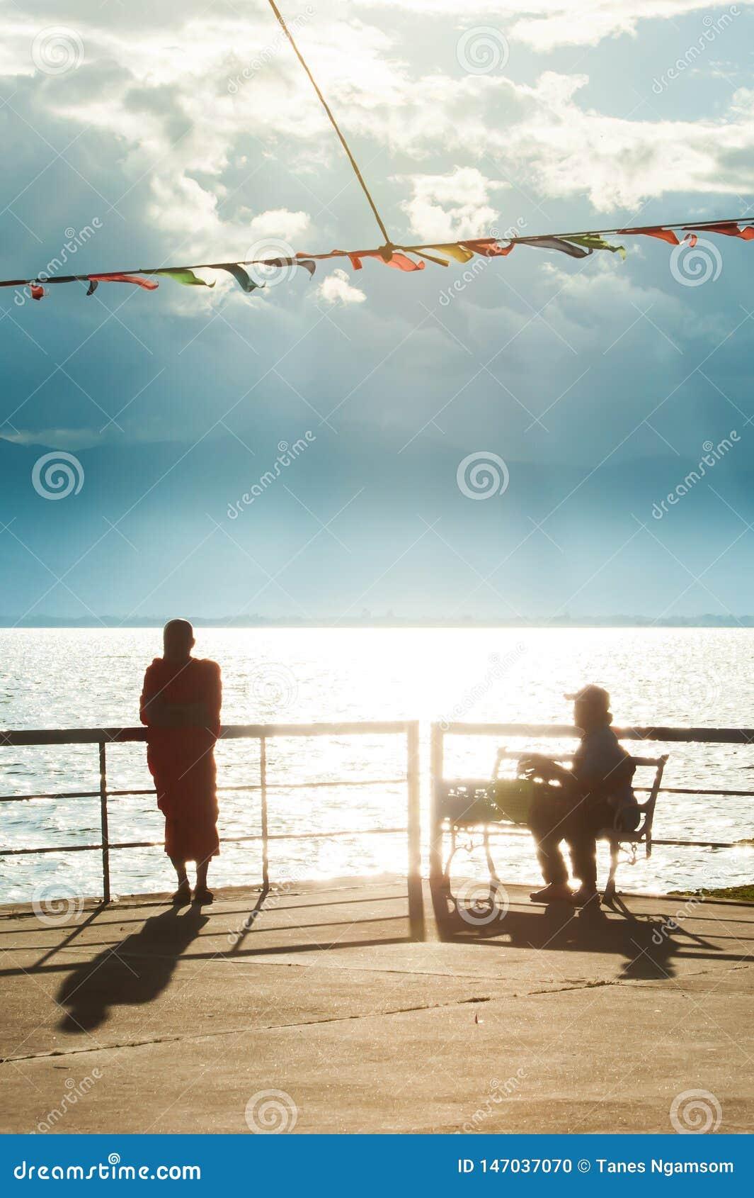 Sch?ne Sommerzeit, ruhiges szenisches des Seeufers an der D?mmerung, buddhistische M?nche und Leute, die im Sonnenunterganglicht,