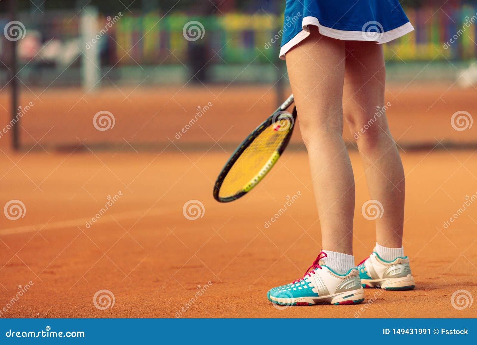 Sch?ner weiblicher Athlet mit dem perfekten K?rper, der oben auf Tennisplatz, Abschluss aufwirft