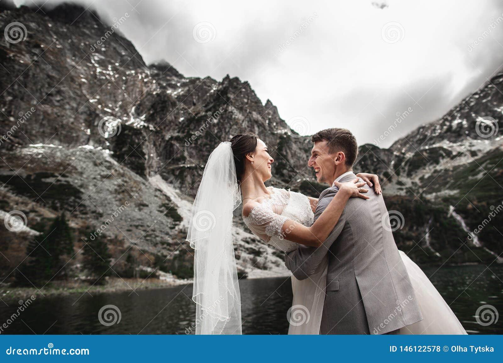 Sch?nes Heiratsphotosession Der Br?utigam kreist seine junge Braut, auf dem Ufer des Sees Morskie Oko ein polen