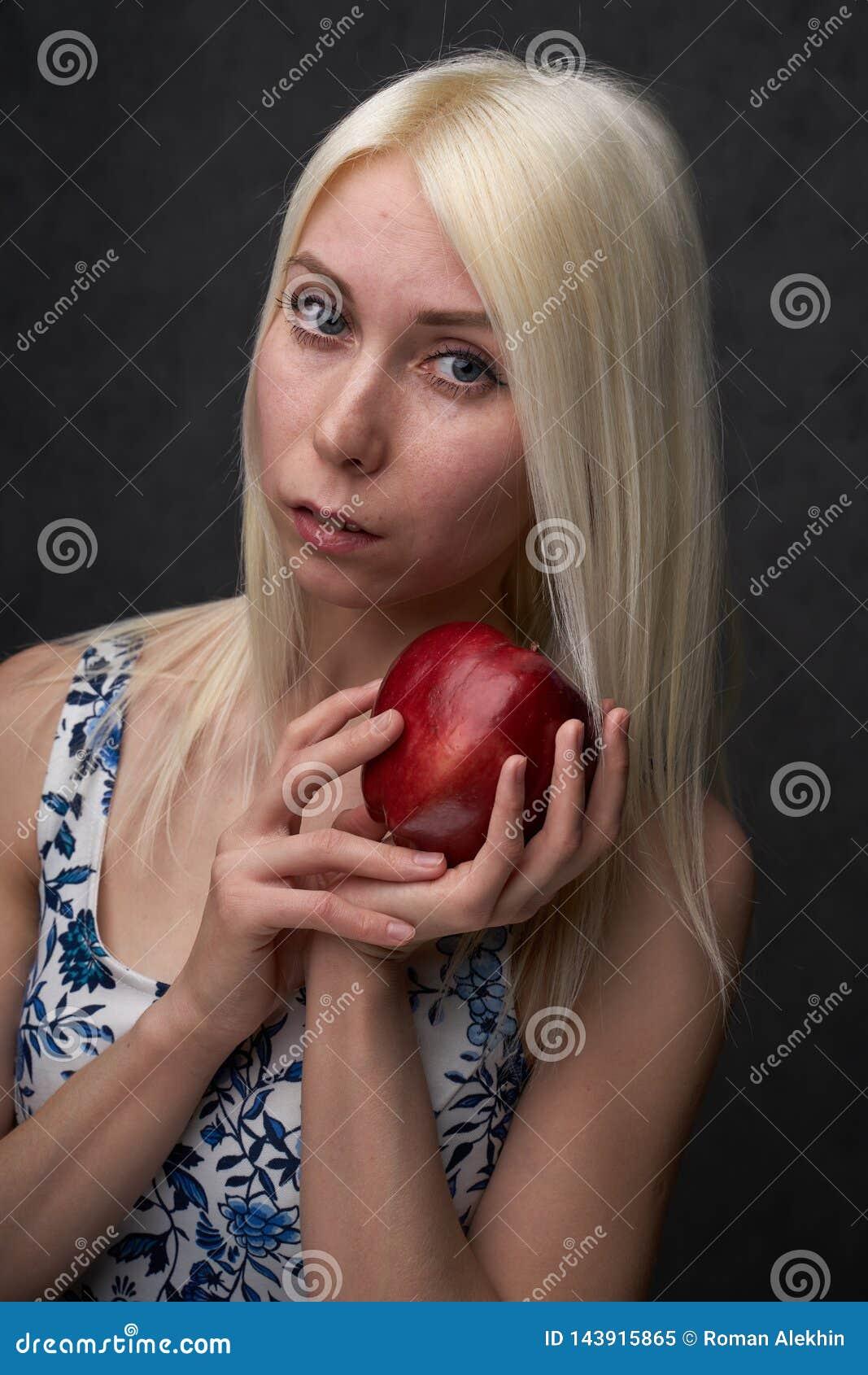 Sch?nes M?dchen in einer modischen Kleidung mit Apfel