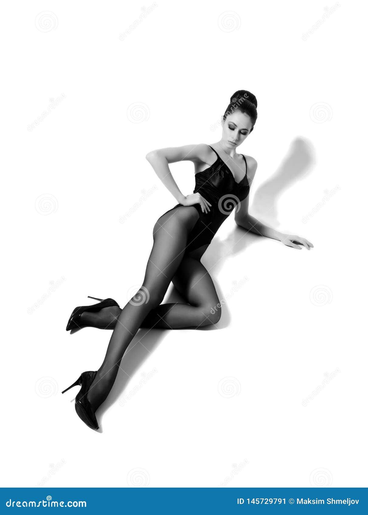 Sch?nes Mode-Modell im schwarzen Badeanzug und in der Strumpfware Junge und Sch?nheit, die im Studio aufwerfen