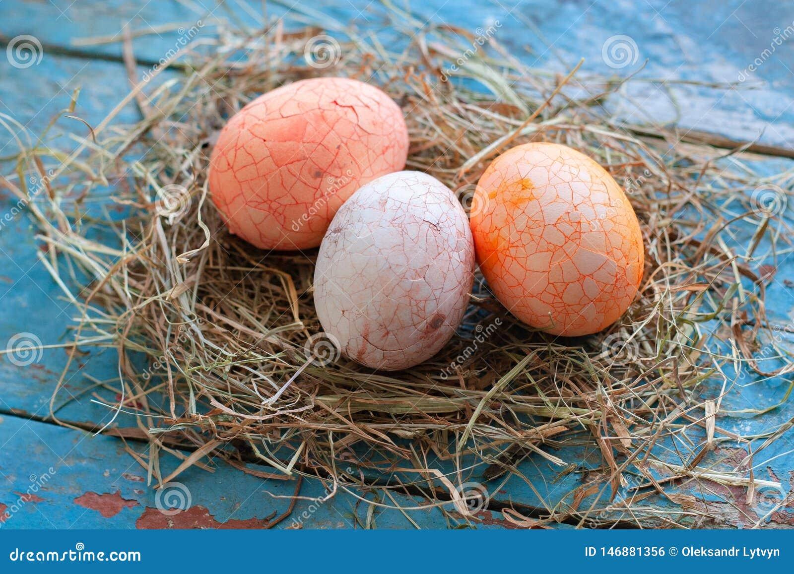 Sch?nes multi Farbei Ostern im Stroh auf h?lzernem Hintergrund, Ostern-Tageskonzept