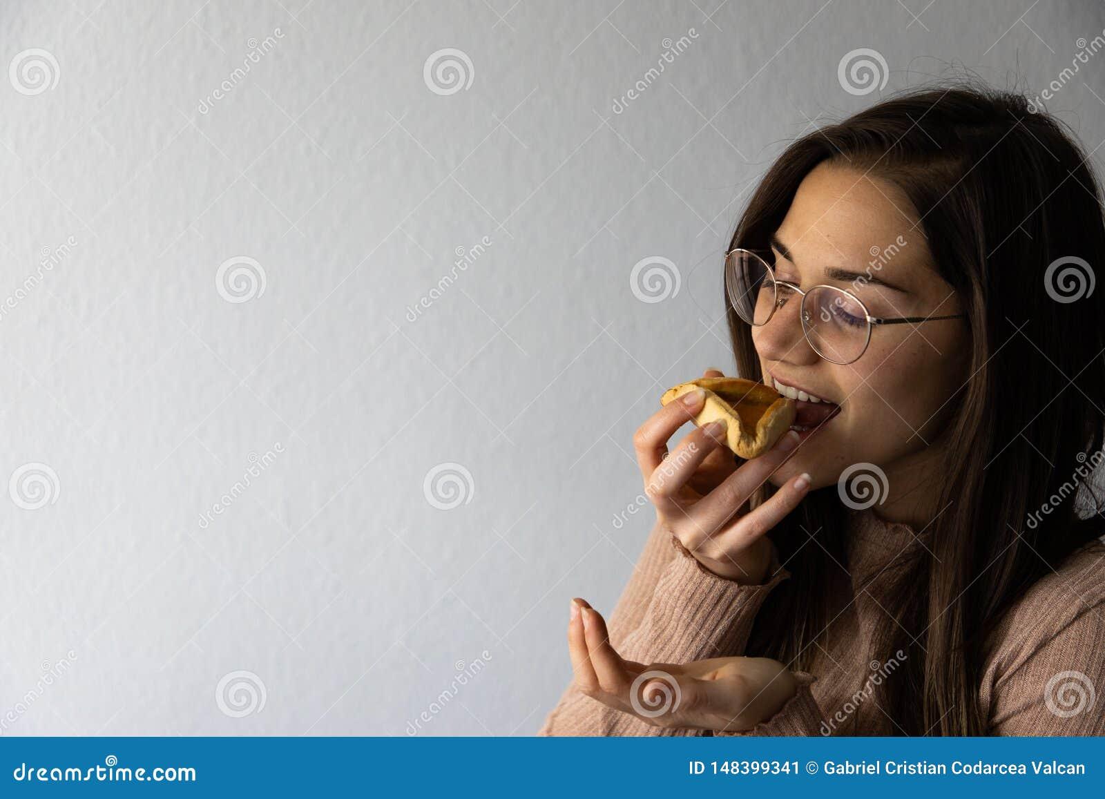 Sch?nes und gl?ckliches Frauenportr?t, das hamantash Purim-Aprikosenpl?tzchen isst