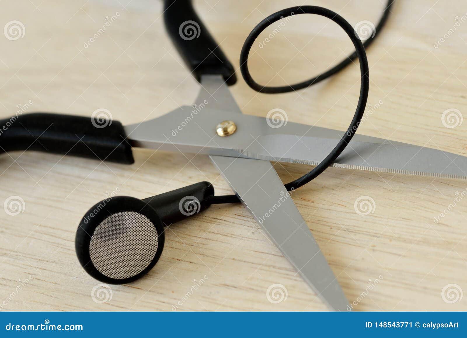 Schaar die de draad van hoofdtelefoons snijden - oortelefoons Concept het luisteren en mededeling, draadloze hoofdtelefoons