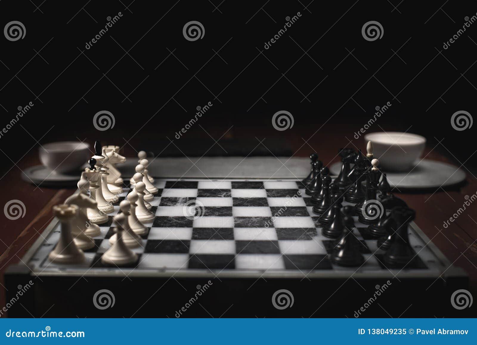 Schackstycken på schackbrädet Mörk bakgrund och rök