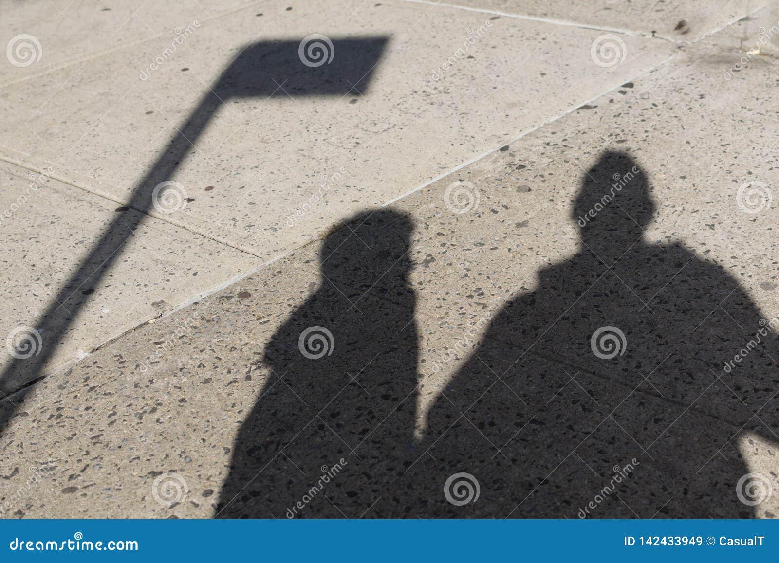 Schaduwen van een vader en zijn zoon op een ruwe concrete straat