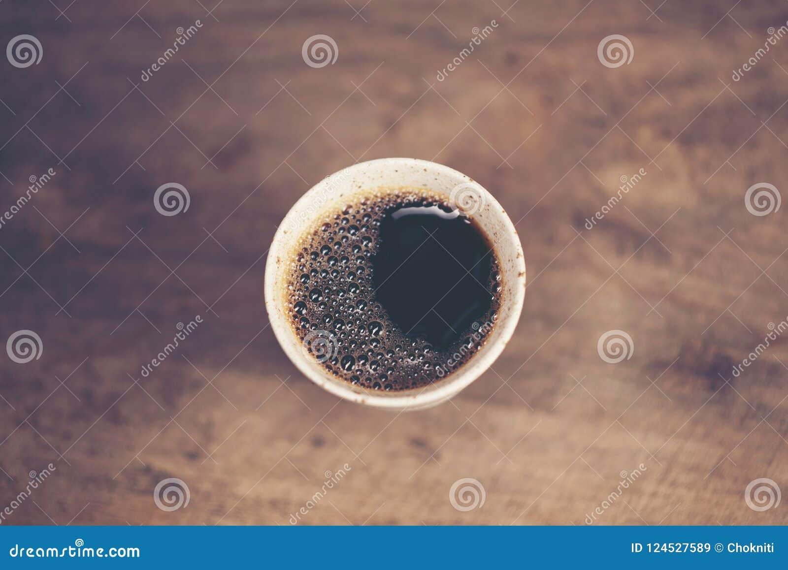 Schale des Tropfens des frischen heißen Kaffees auf der hölzernen Tabelle