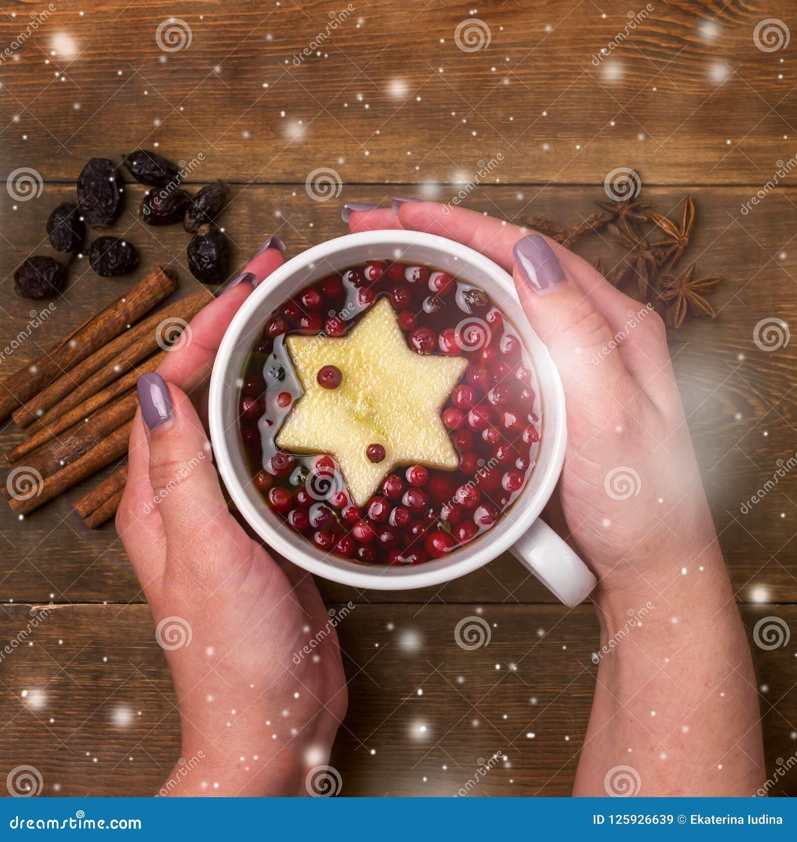 Schale heißer Tee mit Beere und Apple-Zimt würzt die hölzernen Hintergrund Weihnachtslebensmittel-Konzept-Draufsicht-weiblichen H