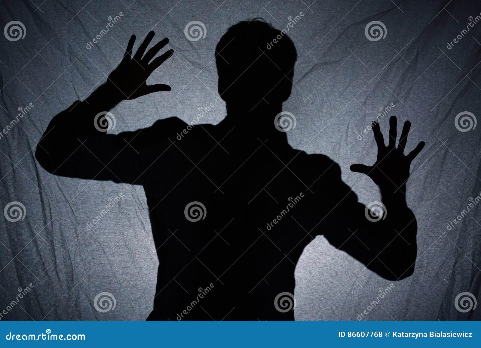 Schatten des Mannes hinter dunklem Gewebe