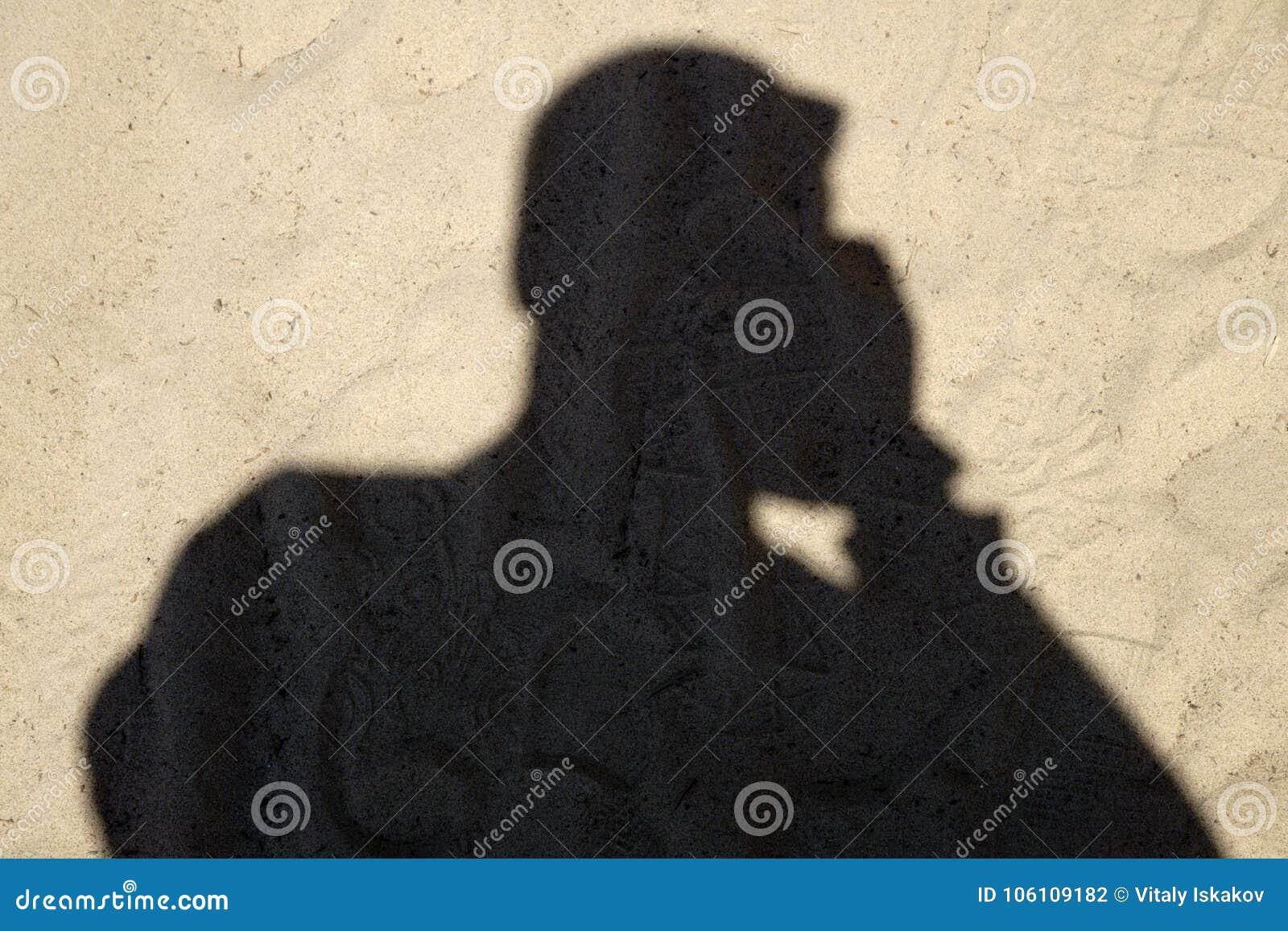 Schatten des Mannreisenden mit Rucksack machen Foto auf Sandstrand zur Sonnenuntergangzeit, Reise herein