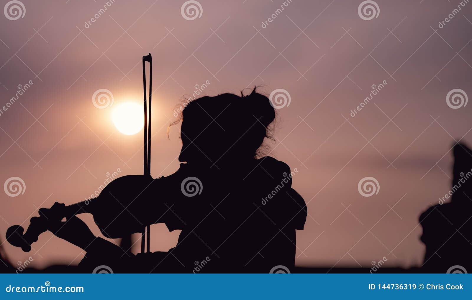 Schattenbild der Frau die Violine während des Sonnenuntergangs gegen das sonnen- eingelassene Prag spielend