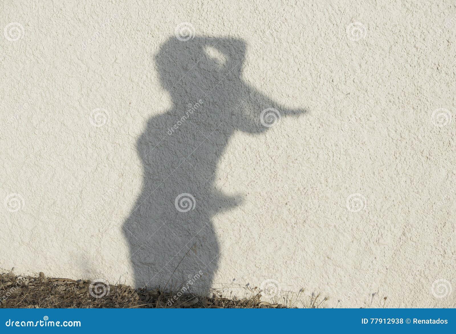 Schattenbild der Frauenzahl auf natürlichem Wandhintergrund Frauen stellen auf einer Wand, künstlerisches Foto dar Kontrast, Scha