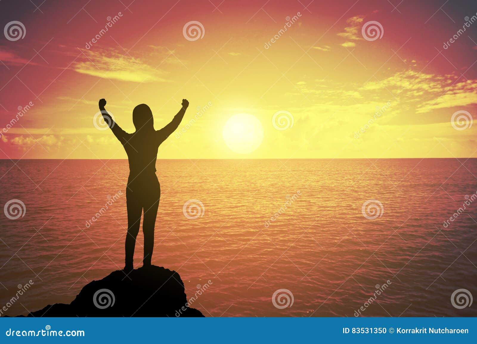 Schattenbild der gewinnenden Erfolgsfrau bei dem Sonnenuntergang oder Sonnenaufgang, die oben Hand zur Feier des Erreichens des B