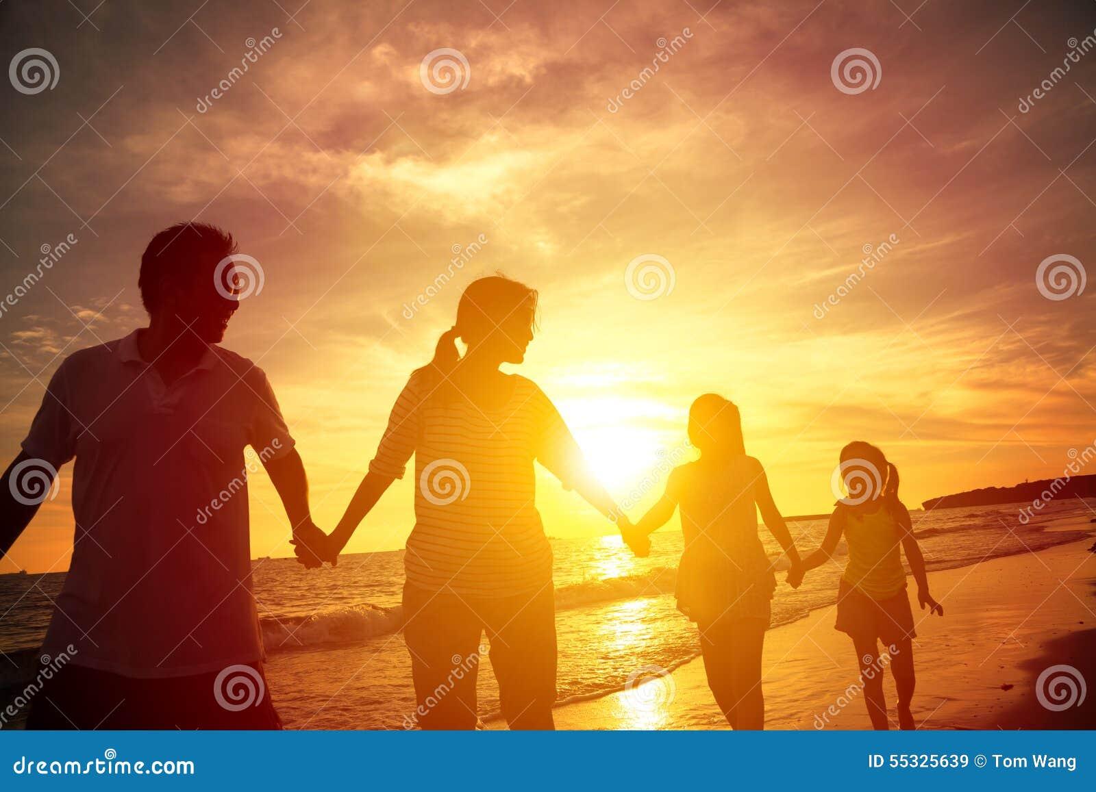Schattenbild der glücklichen Familie gehend auf den Strand