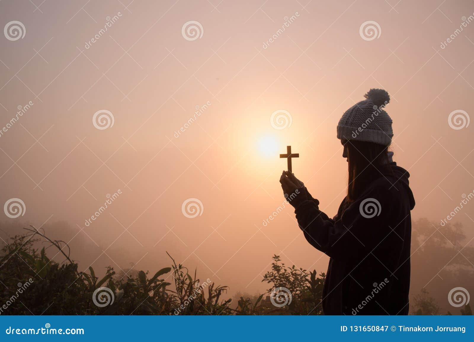 Schattenbild der jungen Frau betend mit einem Kreuz bei Sonnenaufgang, Christian Religions-Konzepthintergrund