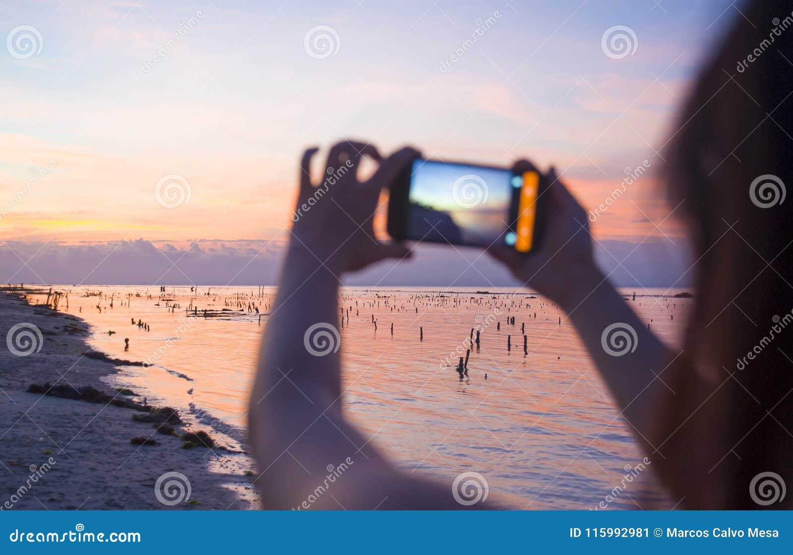 Schattenbild der jungen Frau mit der Handykamera, die Foto schönen Strandsonnenunterganglandschaft- und -berg Agungs-Vulkans von