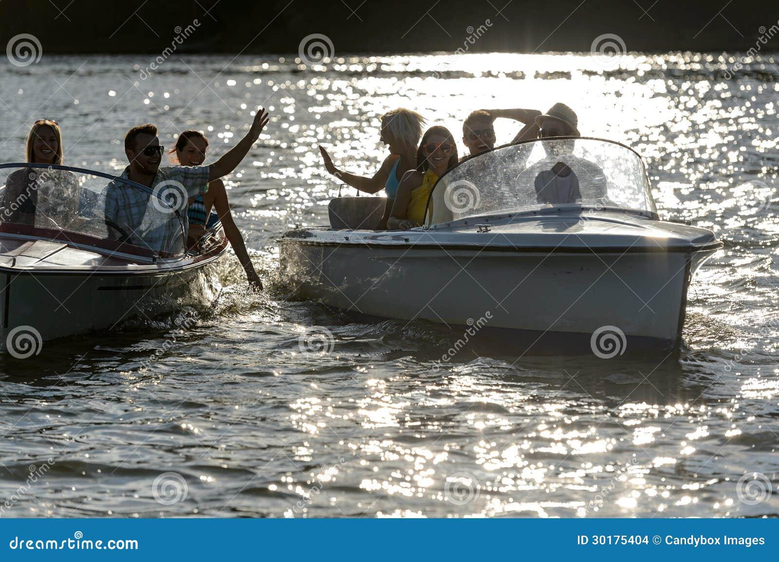 Schattenbild der jungen Freunde in den Motorbooten
