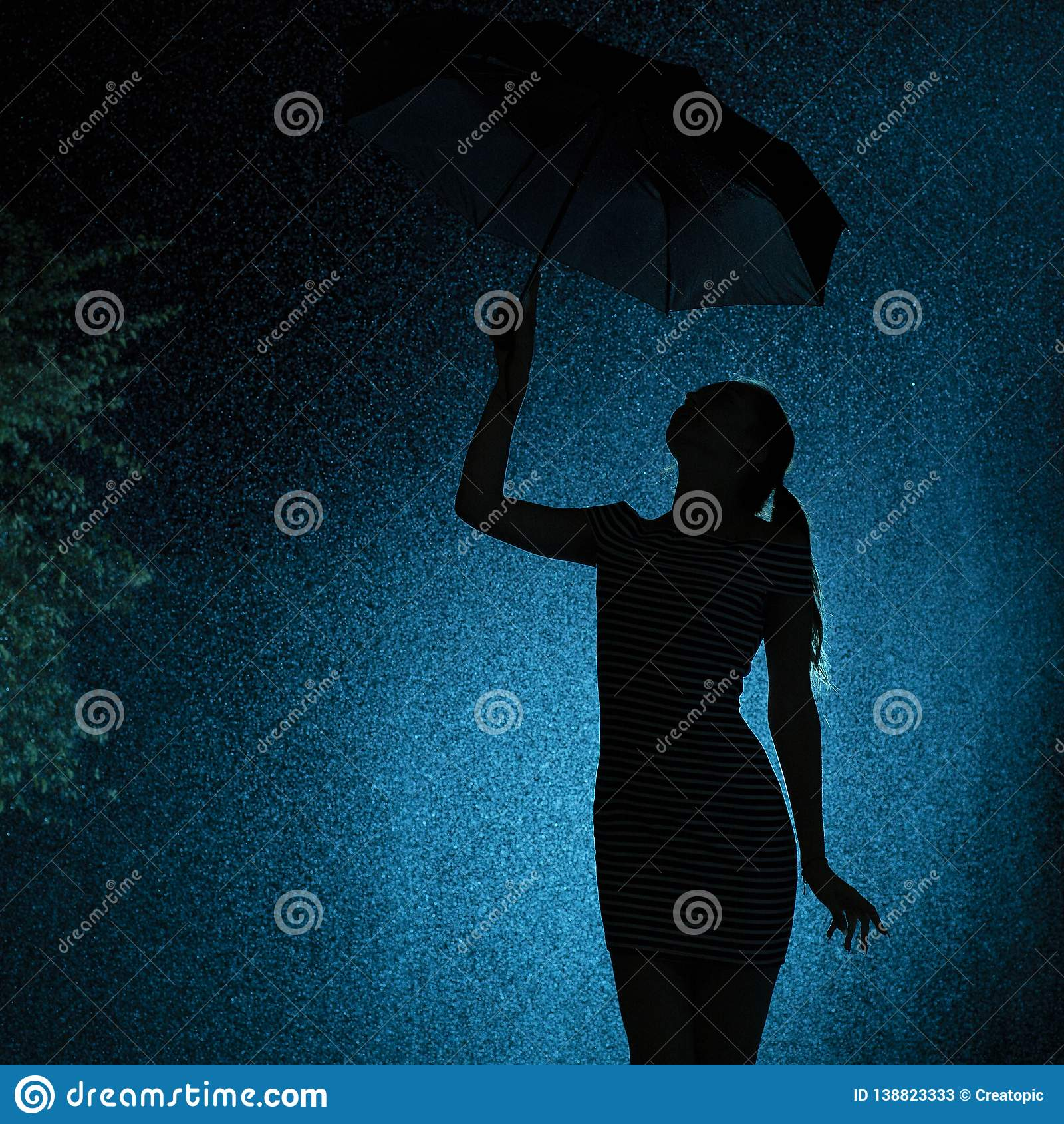 Schattenbild der Zahl eines jungen Mädchens mit einem Regenschirm im Regen, eine junge Frau mit dem handverlesenen Haar ist zu de