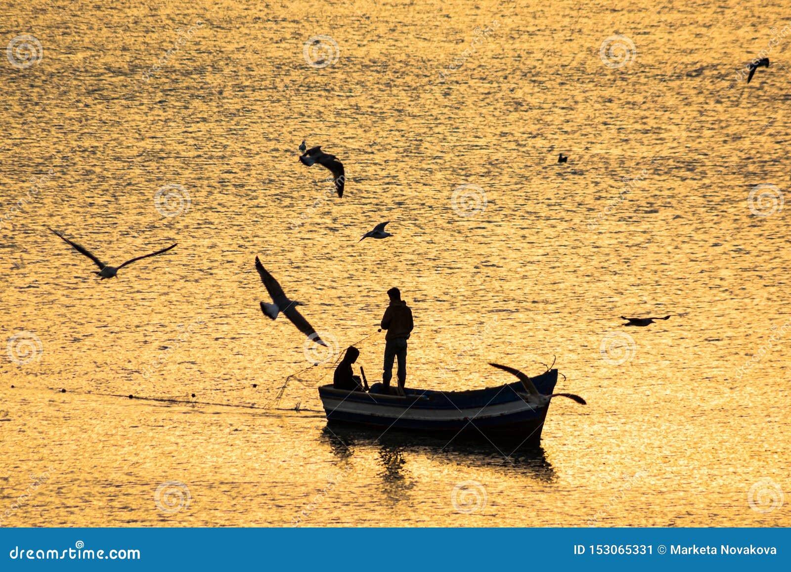 Schattenbild des Fischerbootes auf Mittelmeer während des Sonnenaufgangs in den goldenen Sonnenstrahlen in Marokko