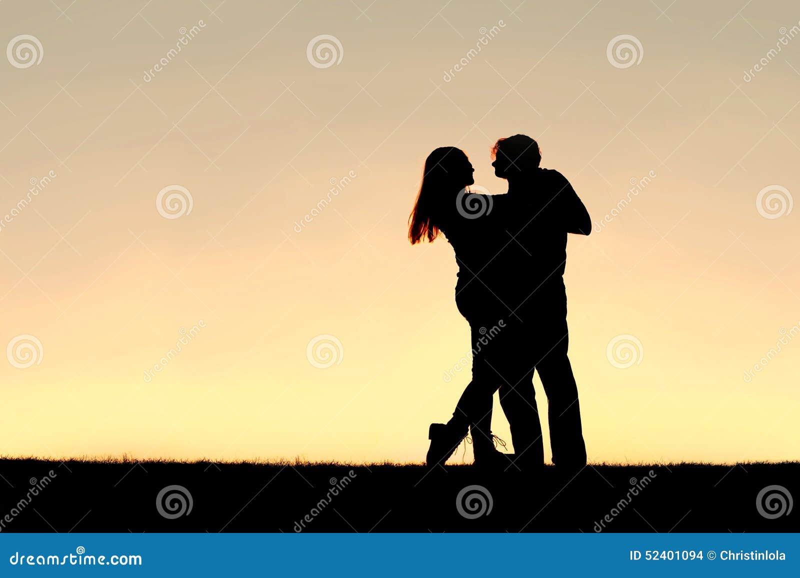 Schattenbild des glücklichen jungen Paar-Tanzens bei Sonnenuntergang
