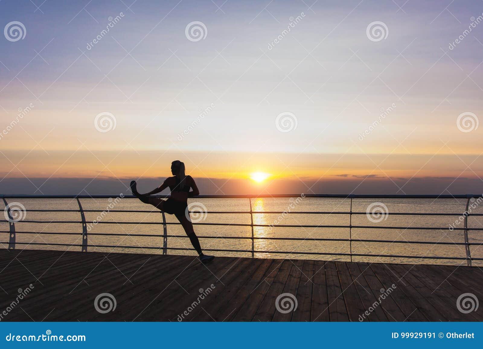 Schattenbild des jungen schönen athletischen Mädchens mit dem langen blonden Haar in den Kopfhörern hörend Musik und das Ausdehne