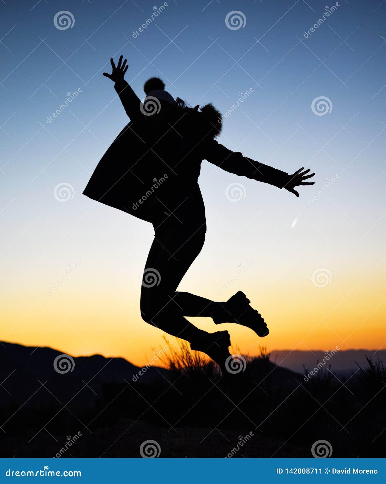 Schattenbild des Mädchens springend mitten in Natur auf Winter gegen Sonnenuntergang