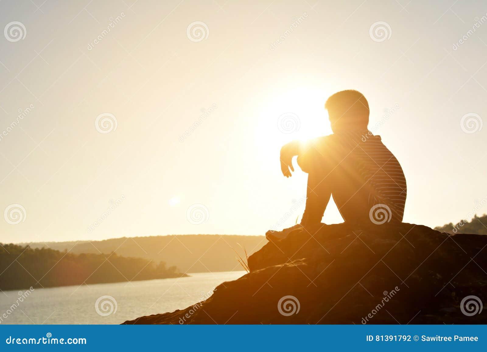 Schattenbild des traurigen Jungen und des Sitzens auf dem Felsen im Fluss
