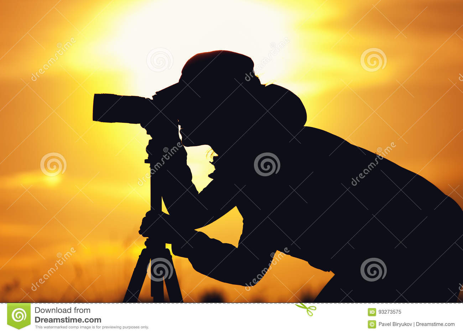 Schattenbild des weiblichen Fotografen gegen Sonnenuntergang