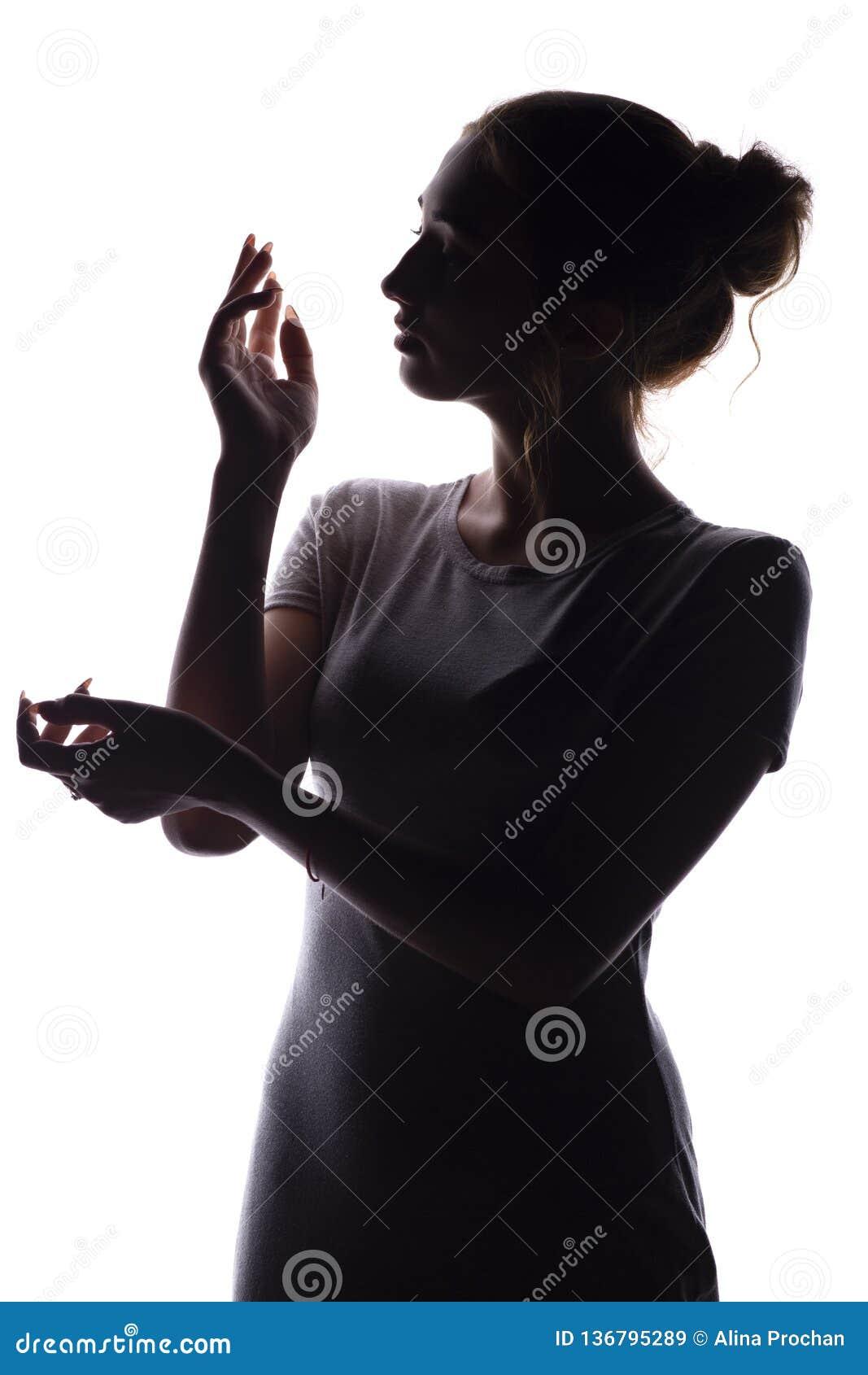 Schattenbild einer jungen Frau, die wie eine Puppe, die Zahl einer jungen Frau mit den würdevoll gesetzten Händen aufwirft