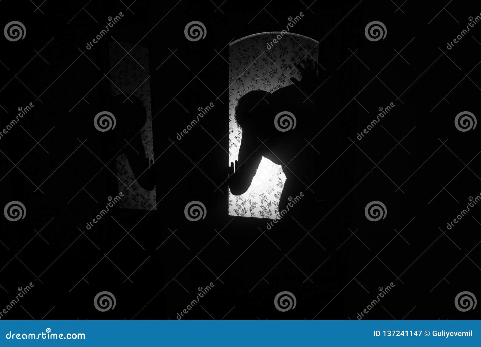 Schattenbild einer unbekannten Schattenzahl auf einer Tür durch eine geschlossene Glastür Das Schattenbild eines Menschen vor ein