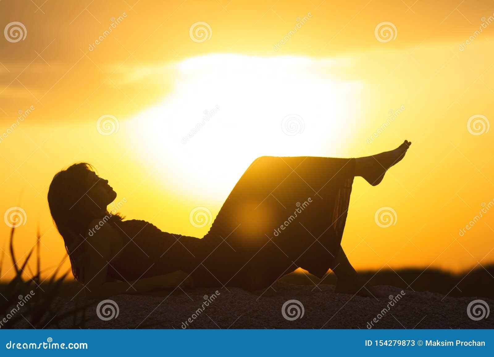 Schattenbild eines jungen schönen Mädchens, das in einem Kleid auf dem Sand liegt und den Sonnenuntergang, die Frauenfigur auf de