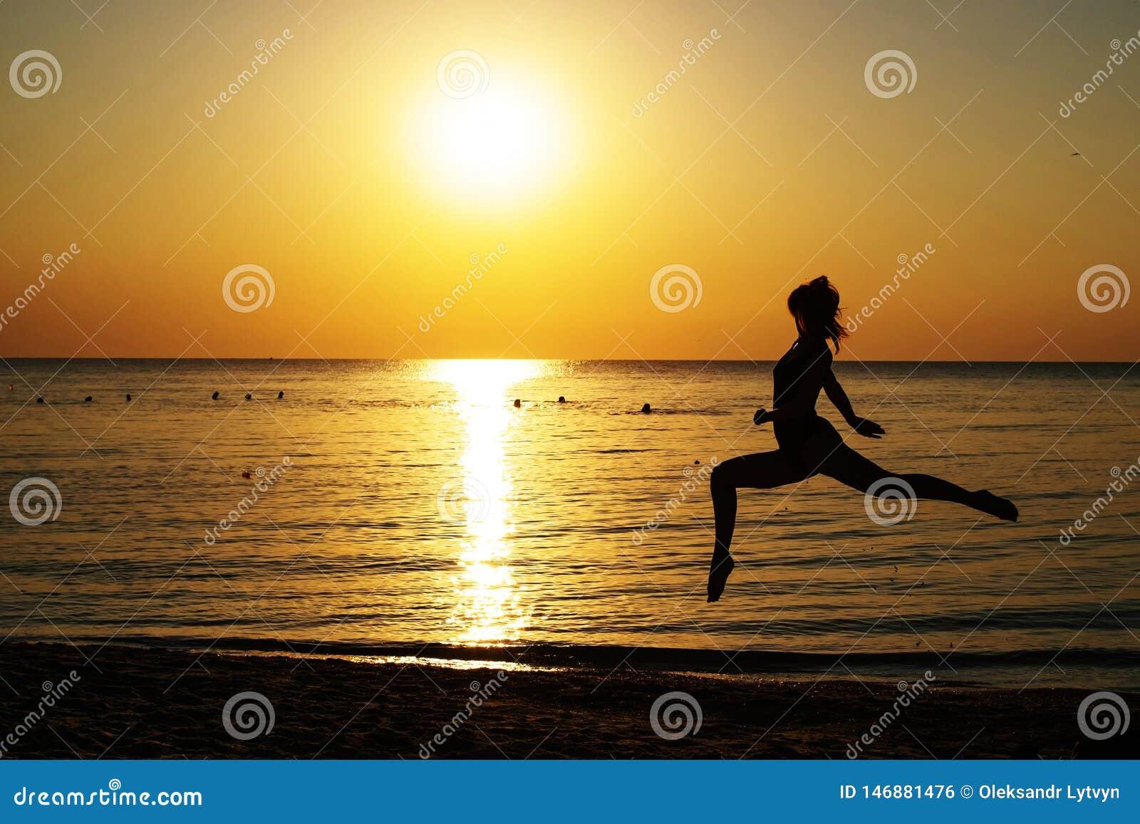 Schattenbild eines M?dchens in einem Badeanzug, der entlang den Strand auf dem Hintergrund der D?mmerung l?uft