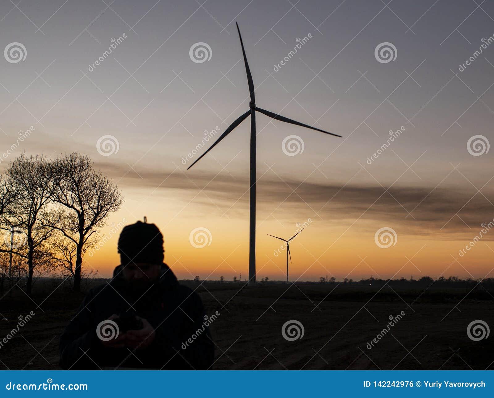 Schattenbild eines Mannes bei dem Sonnenuntergang, der ein Foto von den Windkraftanlagen macht Windkraftanlagen bei Sonnenunterga