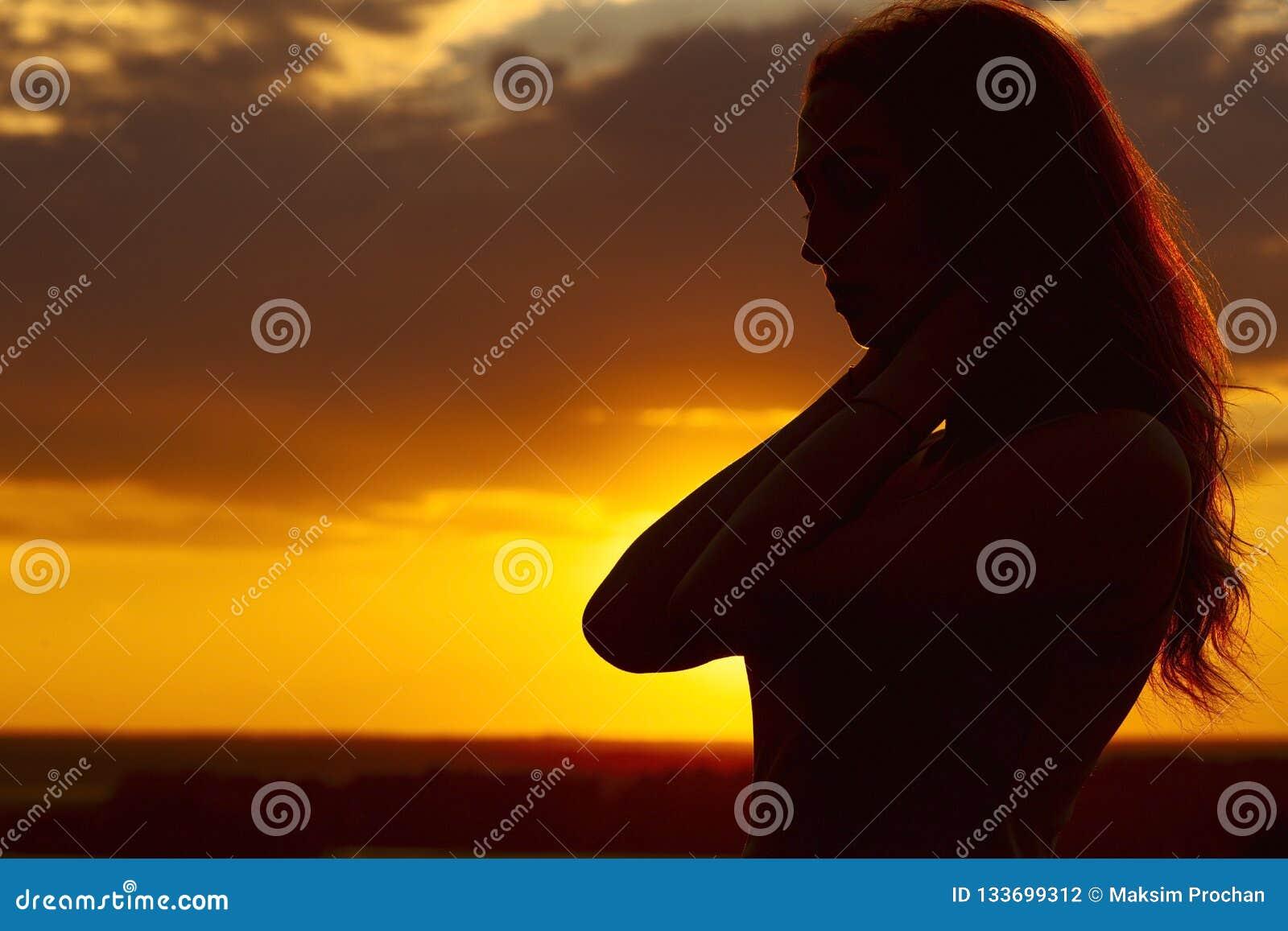Schattenbild eines schönen romantischen Mädchens bei Sonnenuntergang, Gesichtsprofil der jungen Frau mit dem langen Haar bei heiß