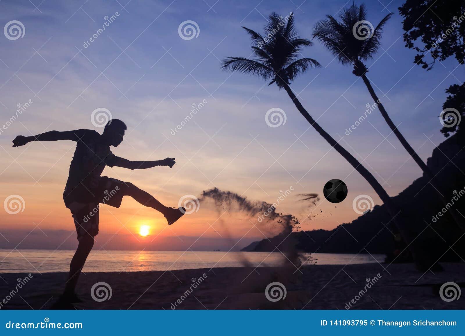 Schattenbild-Salven-Trittfußball auf dem Strand, asiatischer Mannspielfußball bei Sonnenaufgang