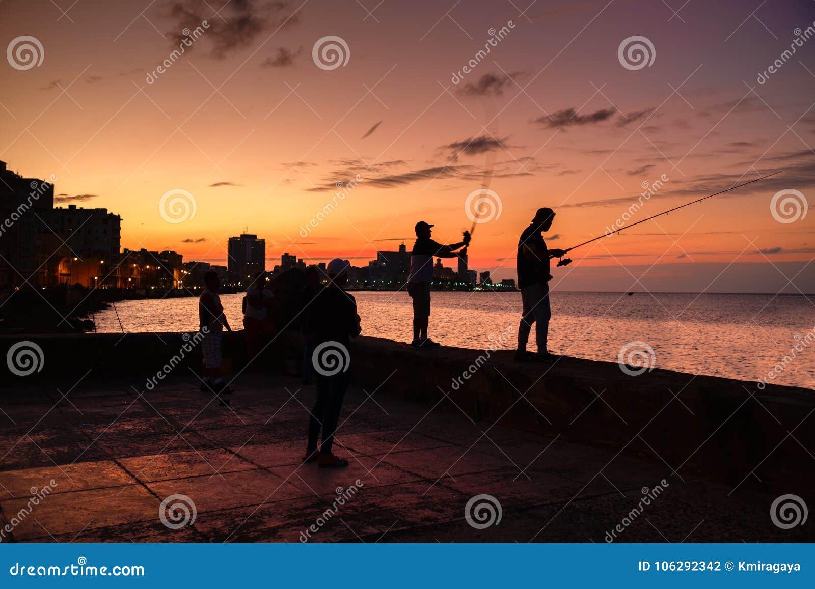 Schattenbild von Fischern und die Stadtskyline in Havana