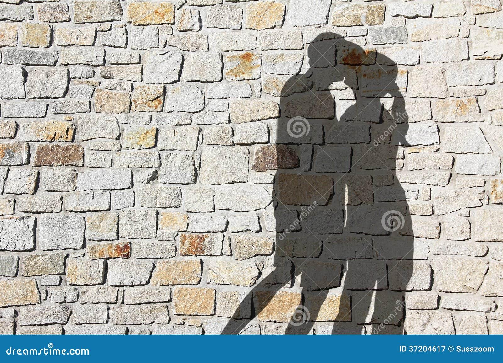 Schattenbild von küssenden paaren, gegen natursteinwand ...