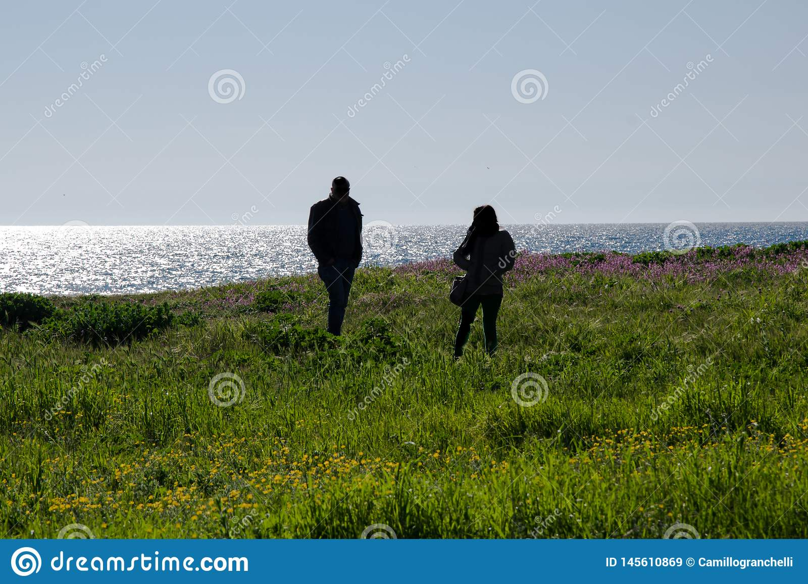 Schattenbild von Leuten mit Seehintergrund