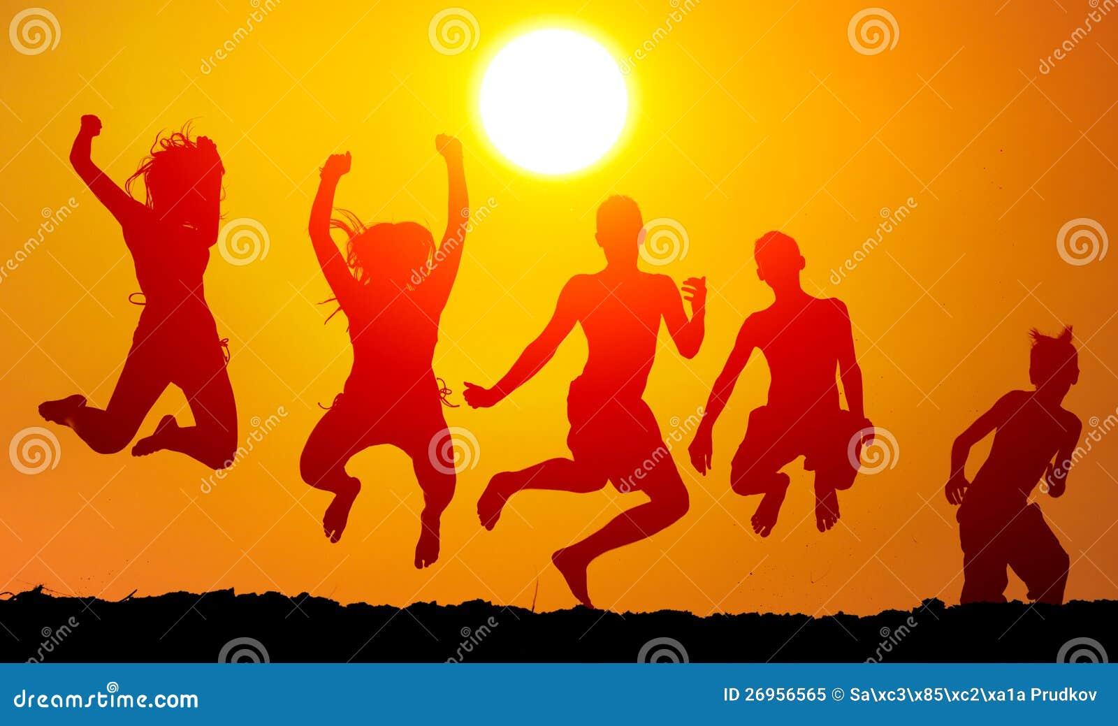 Schattenbilder der glücklichen Jugendlichen, die hoch springen