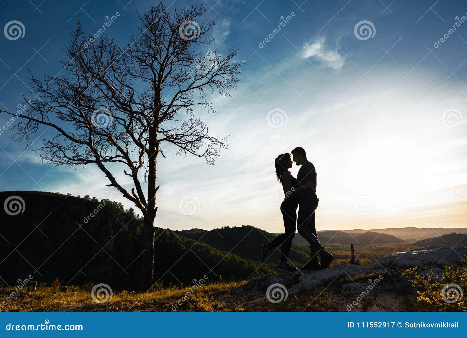 Schattenbilder der liebevollen Paare am Sonnenuntergang