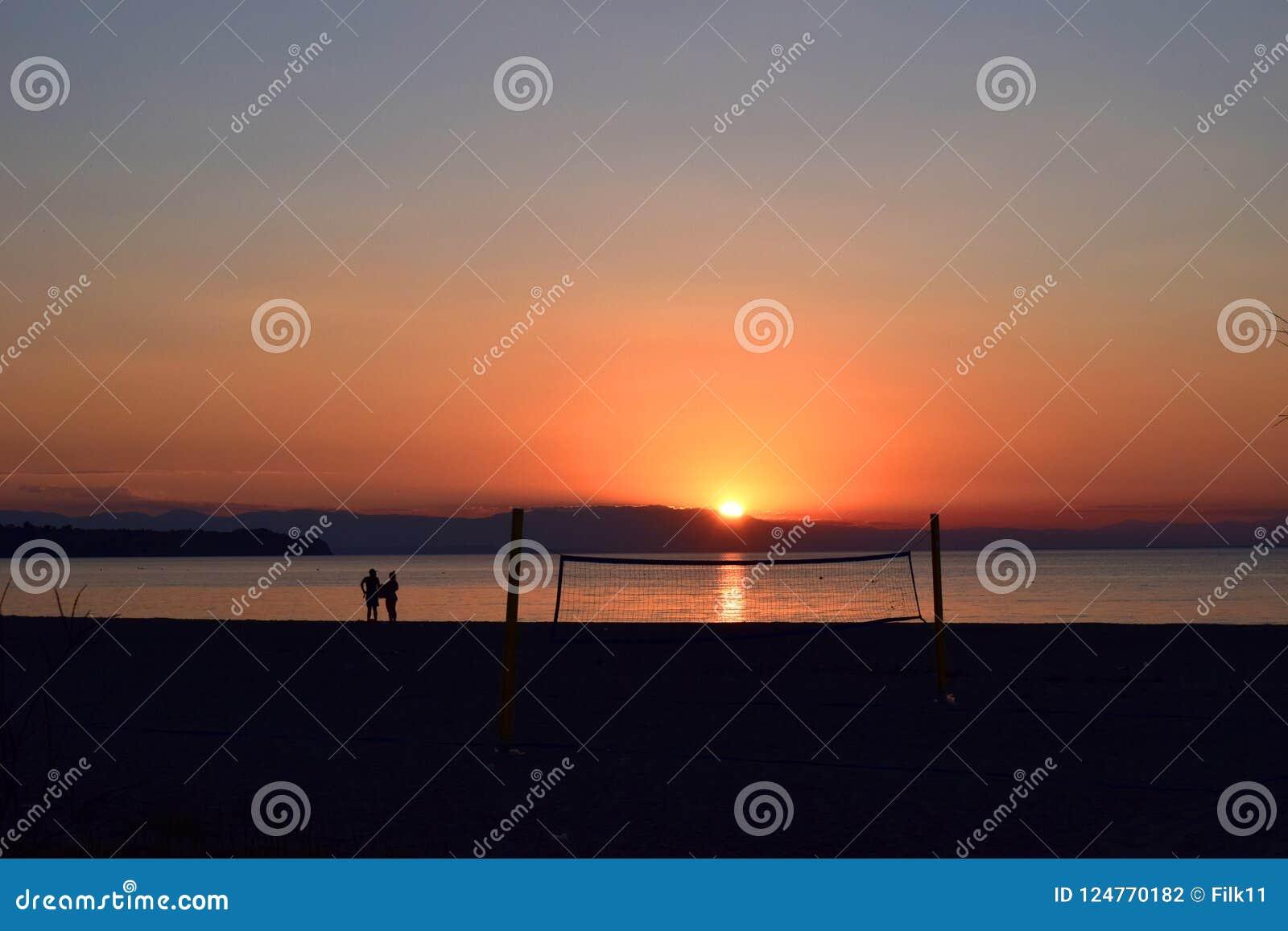 Schattenbilder nahe bei einem Volleyballnetz auf dem Strand Schöner Sonnenuntergang in Griechenland