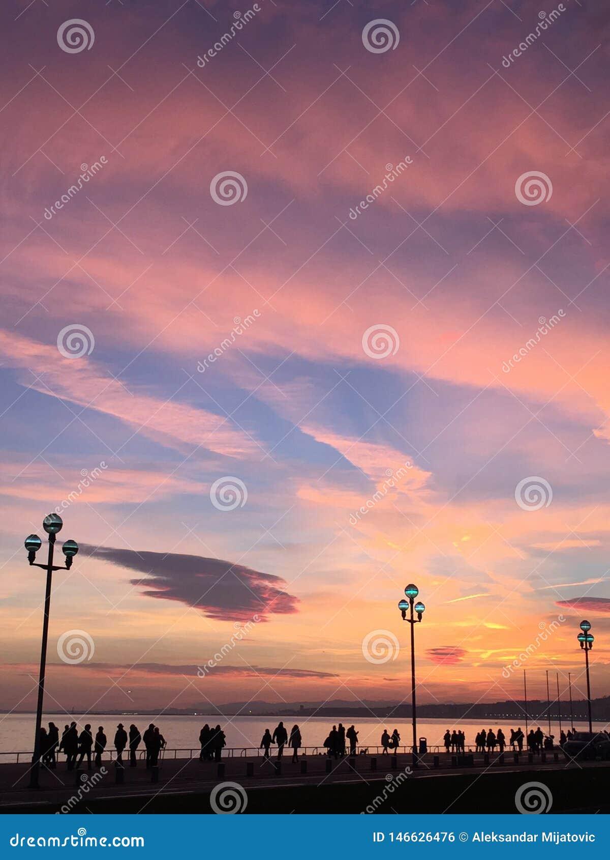 Schattenbilder von den Leuten, die am sundusk nahe Strand in Nizza Frankreich gehen