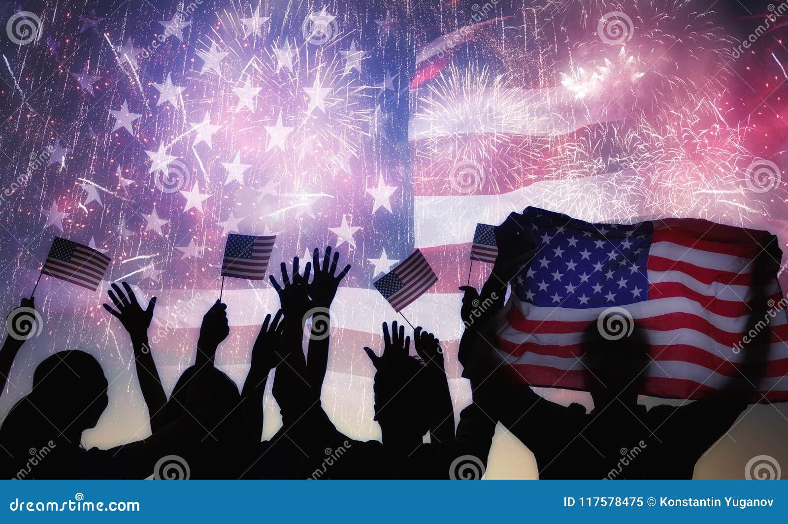 Schattenbilder von den Leuten, welche die Flagge der USA halten