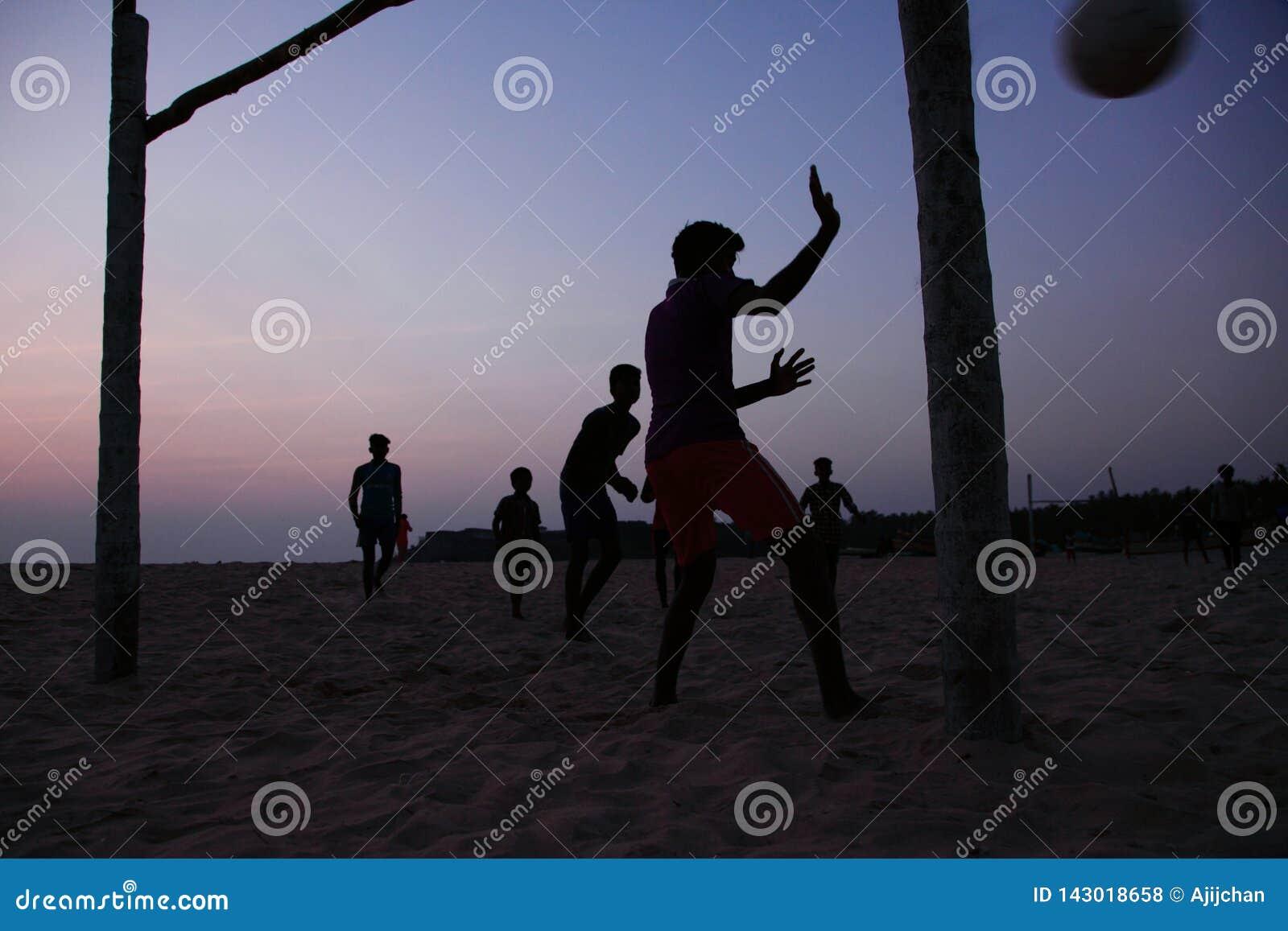 Schattenbilder von Leuten spielen Fußball im Strand